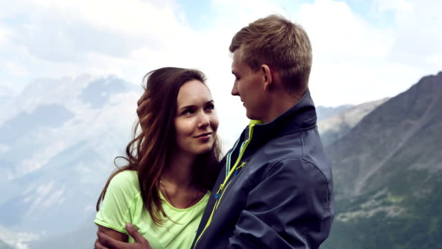 reaching the summit. happy couple hugging on the mountain top - young couple stock videos & royalty-free footage