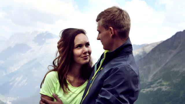 den gipfel zu erreichen. glückliches paar umarmt auf des berges höhn - junges paar stock-videos und b-roll-filmmaterial