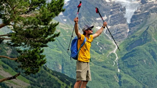 vídeos de stock, filmes e b-roll de atingir o cume. homem feliz, de pé no topo da montanha - mãos estendidas