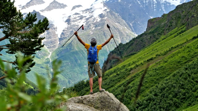 reaching the summit. happy man standing on the mountain top - human limb stock videos & royalty-free footage