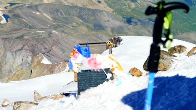 nå toppen. bön flaggor och vandring pole på toppen - klätterutrustning bildbanksvideor och videomaterial från bakom kulisserna