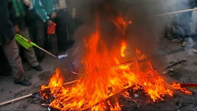 reaction in iran to barack obama presidency; tehran: ext anti-american demonstrators burning items on fire in street int muslim men praying close... - president stock videos & royalty-free footage