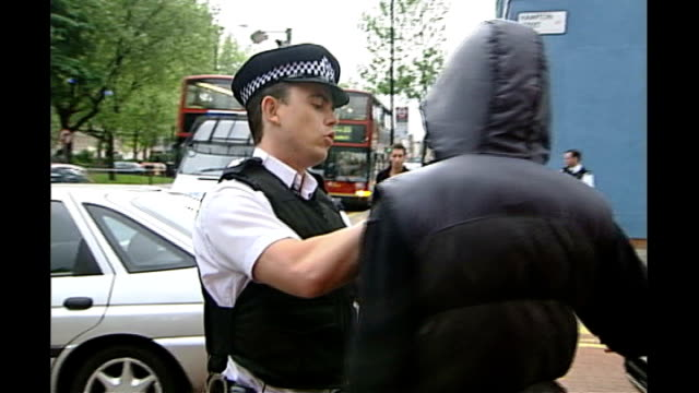 reaction to escalation of stop and search measures in london date police officers searching anonymous hooded youth and using metal detector to check... - säkerhetsskanner bildbanksvideor och videomaterial från bakom kulisserna