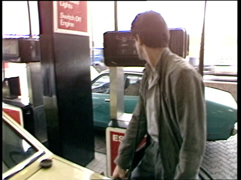 stockvideo's en b-roll-footage met reactions as oil price tumbles to a 13year low due to opec failure to reach agreement over cuts av esso petrol station as yellow british telecom van... - british telecom
