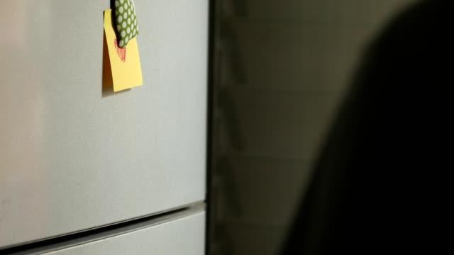 vidéos et rushes de lire les notes post-it sur le réfrigérateur. - réfrigérateur