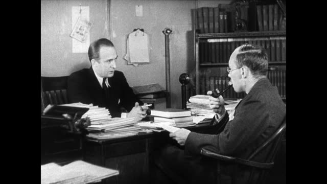 reader's digest magazine publisher dewitt wallace seated at desk talking w/ writer joseph furnas telling him he wants a 'real' piece written about... - 1935 stock-videos und b-roll-filmmaterial