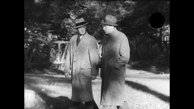 reader's digest magazine publisher & philanthropist dewitt wallace in coat hat walking w/ writer joseph furnas outside. - rivista pubblicazione video stock e b–roll