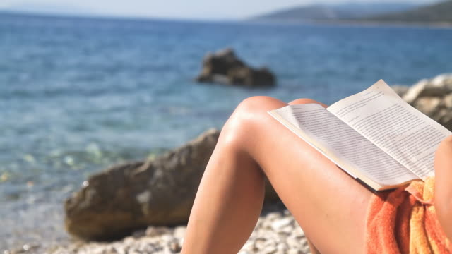 hd: reading a book on the beach - summer reading stock videos & royalty-free footage