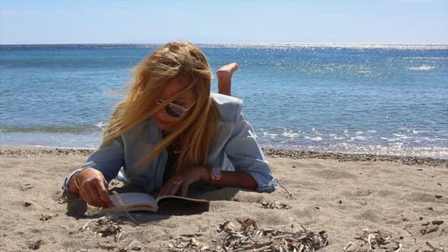 vídeos de stock, filmes e b-roll de lendo um livro na praia - reading berkshire