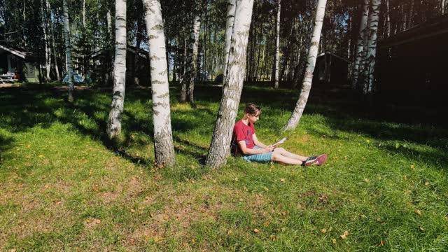 屋外で本を読む - カバノキ点の映像素材/bロール