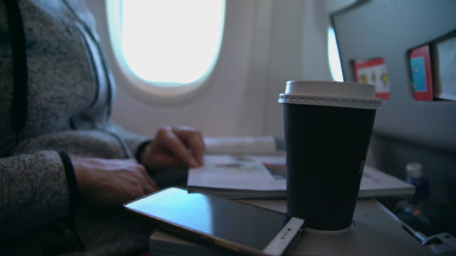 MS Reading a magazine and drinking a coffee on the flight
