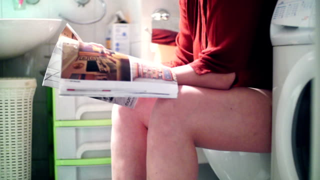 reading a magazine in bathroom. - toilet stock videos and b-roll footage