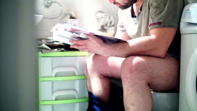 reading a magazine in bathroom. - magazine publication stock videos & royalty-free footage