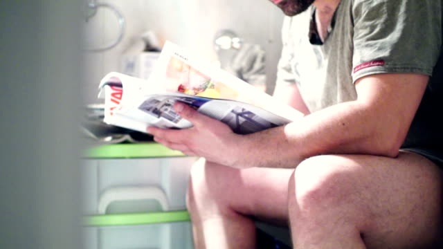 reading a magazine in bathroom. - magazine stock videos & royalty-free footage