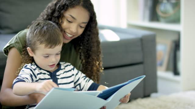 vídeos de stock e filmes b-roll de reading a storybook - cuidar de crianças