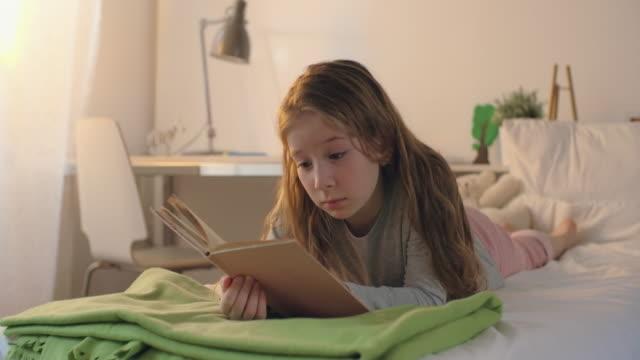 vídeos y material grabado en eventos de stock de reading before bed - tumbado boca abajo
