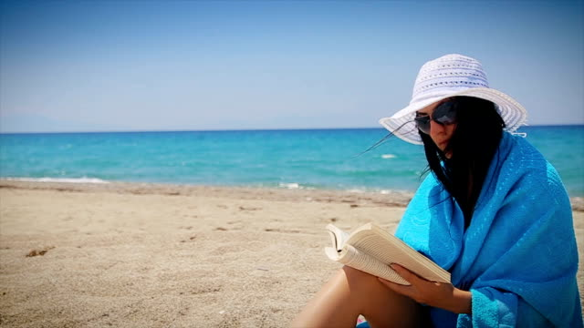 reading book on the beach - cappello video stock e b–roll