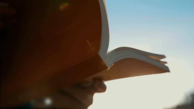 buch mit sonnenuntergang sommerlicht - buchdeckel stock-videos und b-roll-filmmaterial