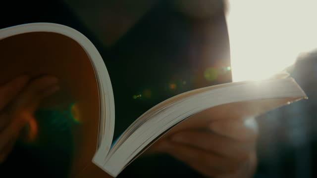 vidéos et rushes de lire le livre avec la lumière du coucher du soleil de l'été - couverture de livre