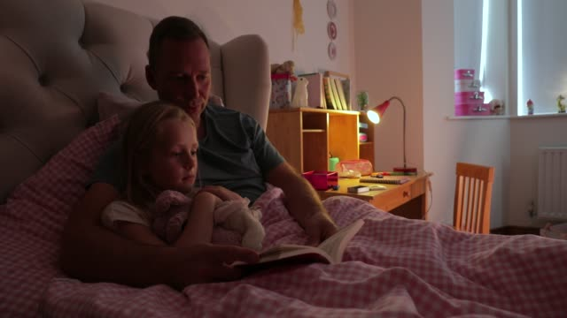 reading his daughter a bedtime story - ora di andare a letto video stock e b–roll
