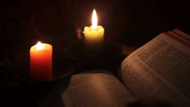Reading Holy Bible In Candle Light
