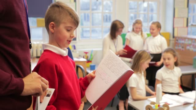 vídeos de stock e filmes b-roll de reading in front of class - criança de escola primária