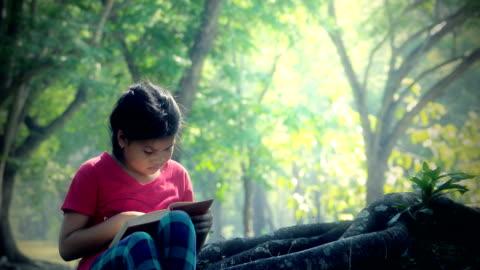 vidéos et rushes de lecture dans le parc - une seule petite fille