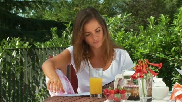 vídeos de stock e filmes b-roll de carrinho de hd: ler a revista após o pequeno-almoço - chaleira de chá