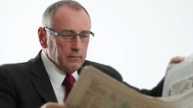 Reading newspaper. Man with glasses.