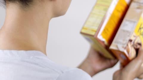 läsa näringsvärdesetikett och jämföra produkter - etikett bildbanksvideor och videomaterial från bakom kulisserna