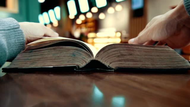 vídeos de stock, filmes e b-roll de leitura do livro velho na tabela - old book