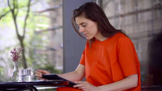 leggere su un tablet in un bar - lettore di libri elettronici video stock e b–roll