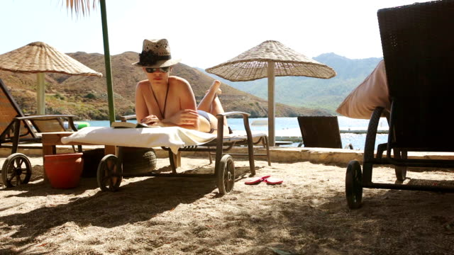 vídeos de stock e filmes b-roll de ler na praia - apanhar sol