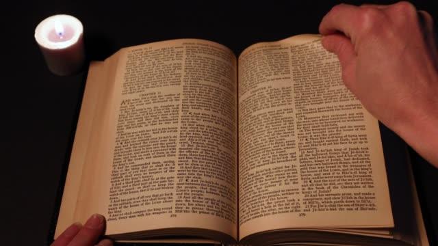 vídeos de stock, filmes e b-roll de lendo a bíblia à luz de velas - bíblia