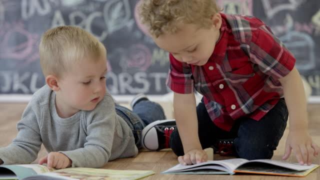 vídeos de stock e filmes b-roll de reading together at daycare - edifício de infantário