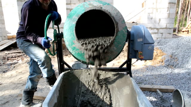 ready concrete pours out of the concrete mixer into the wheelbarrow. - cement mixer stock videos and b-roll footage