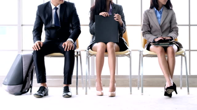 ready to get new career. group of three young businesspeople sitting on chairs in office, waiting and going for job interview, feeling nervous. body language. close up of legs. job search concept - candidate stock videos & royalty-free footage