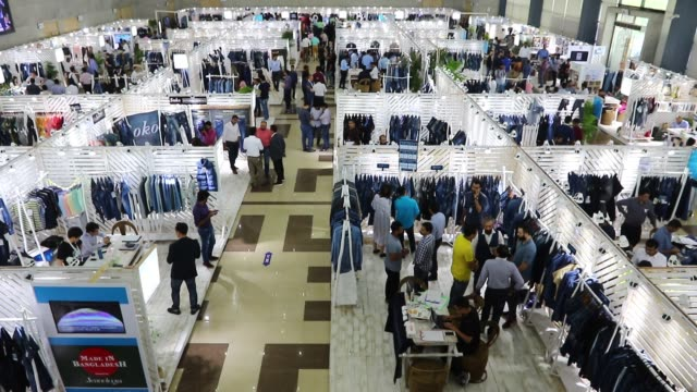 stockvideo's en b-roll-footage met readymade garments product buyers and sellers visit bangladesh denim expo at bashundhara international convention city in dhaka. 10 may 2018.... - clean
