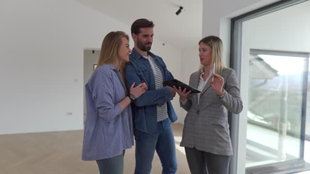 agente immobiliare che mostra proprietà in vendita a giovane coppia sposata - strategia di vendita video stock e b–roll