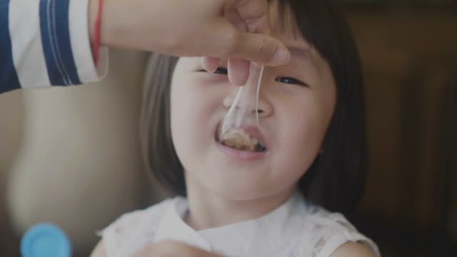 vídeos de stock, filmes e b-roll de o pequeno-almoço do real asiática filha eatting - comida de bebê
