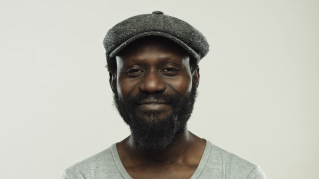 Real black man looking happy against gray background