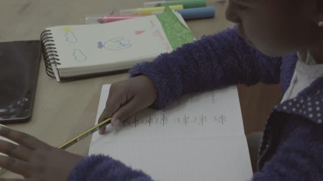 リアルな日常生活: 兄と妹の宿題を家で - 学校備品点の映像素材/bロール