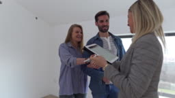 Real Estate Agent congratulating to a young couple for buying a new house.