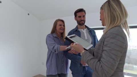 fastighetsmäklare gratulera till ett ungt par för att köpa ett nytt hus. - lägenhet bildbanksvideor och videomaterial från bakom kulisserna