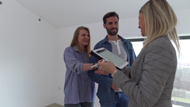 real estate agent congratulating to a young couple for buying a new house. - flat stock videos & royalty-free footage