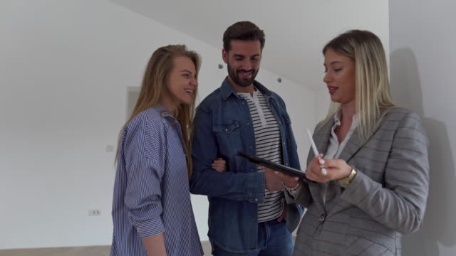 real estate agent explaining to excited young couple architecture of the apartment - sale stock videos & royalty-free footage