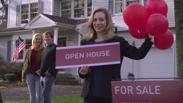 ms td real estate agent holding balloons and open house sign, couple smiling in background / wyckoff, new jersey, usa - estate agent sign stock videos & royalty-free footage