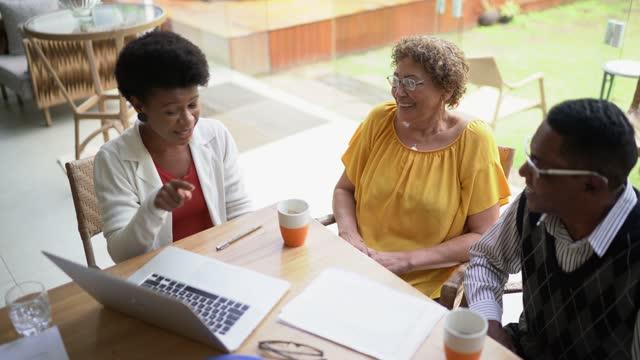 vidéos et rushes de agent immobilier ou conseiller financier faisant une rencontre avec un couple de personnes âgées à la maison - location immobilière