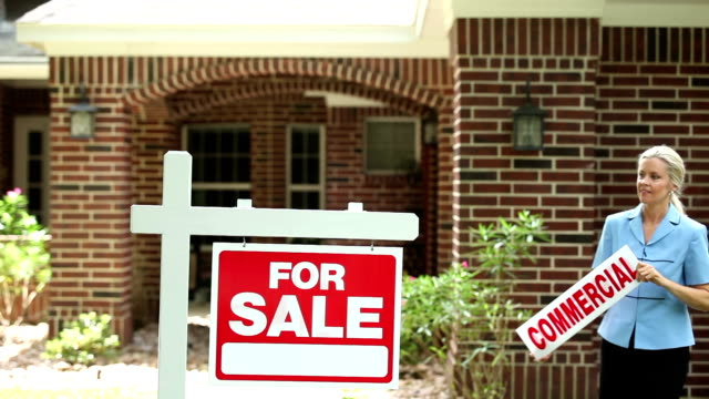 """real estate agent places """"commercial"""" sign. home for sale. - estate agent sign stock videos & royalty-free footage"""