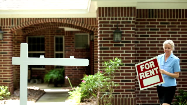 "real estate agent places ""for rent"" sign. home. - house rental stock videos & royalty-free footage"